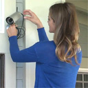 Woman installing surveillance camera